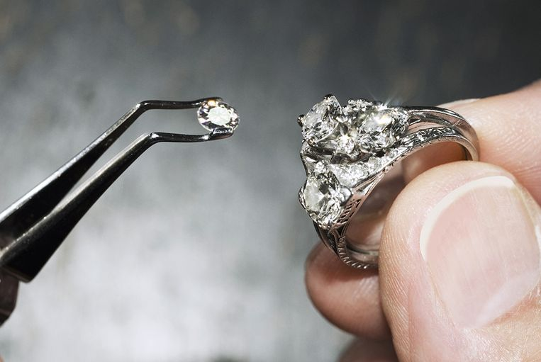 Hands holding diamond ring with gem in tweezers