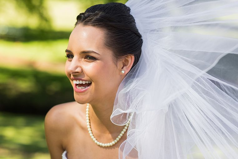 Close-up of a cheerful young beautiful bride in the park